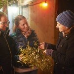 KIWANIS at the Christmas-Market in Erbach: Kiwanis past president Stephanie Uhrig selling mistletoe to customers at the Kiwani-booth, which is the garage of the church-caffe of the protestant church in Erbach.